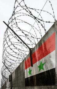Barbwire and grey wall with Syria national flag