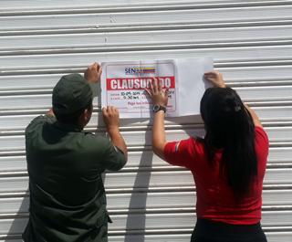 Miembros del Seniat clausurando locales.